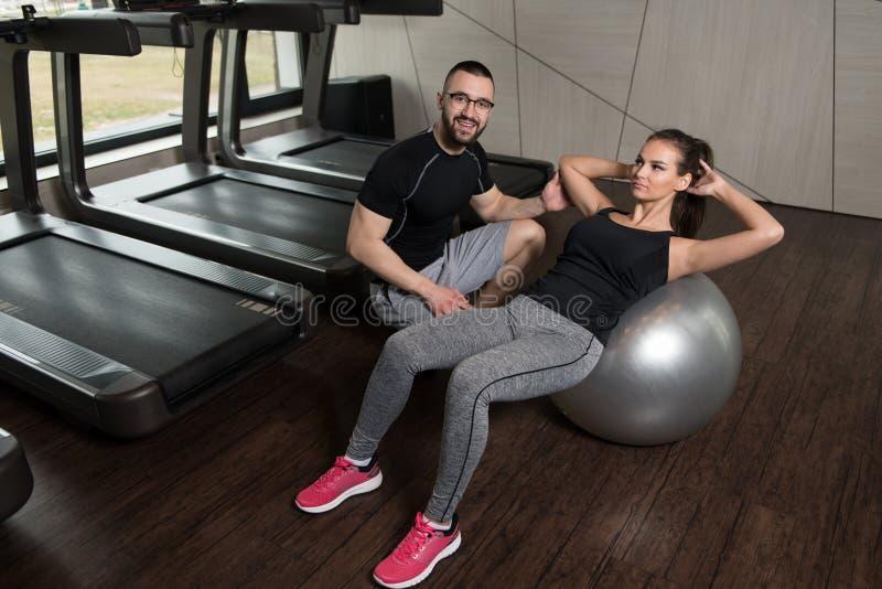 有个人教练员的妇女在球吸收锻炼 免版税库存照片