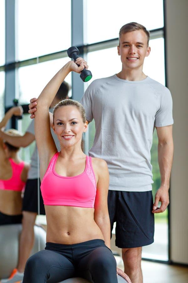 有个人教练员的微笑的少妇在健身房 免版税库存照片