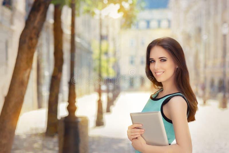有个人计算机片剂的妇女在城市 图库摄影