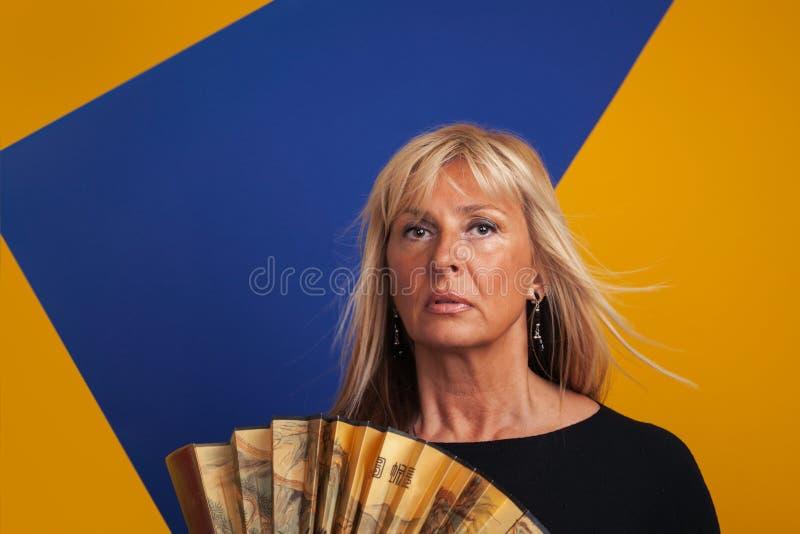 有中年的妇女一个潮热,拿着爱好者 免版税库存照片