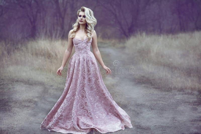有丰富的发型的华美的白肤金发的夫人在长的锦礼服走沿狭窄的道路的在森林 库存照片