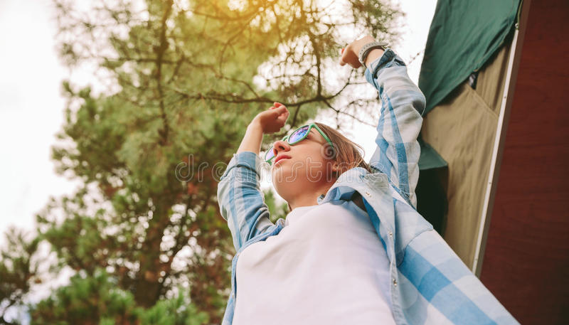 有举她的在自然背景的太阳镜的妇女胳膊 免版税库存图片