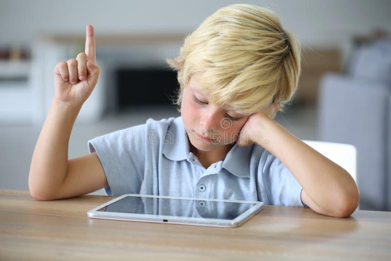 有举手的片剂的小男孩在学校 免版税库存照片
