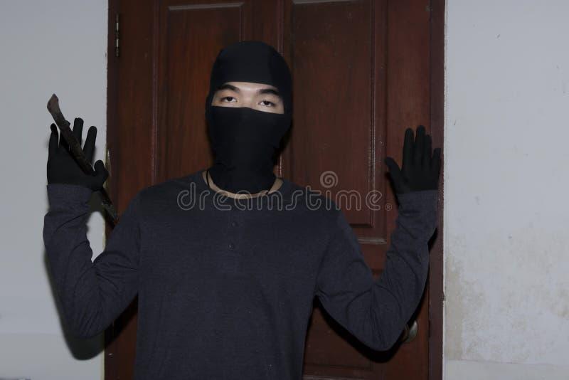 有举手的黑巴拉克拉法帽的窃贼由警察决定 抓住夜贼概念 免版税库存照片