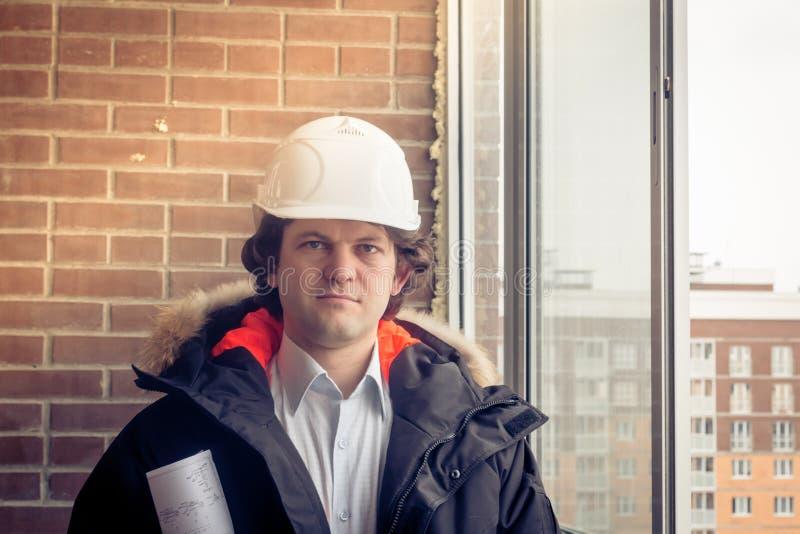 有举行图纸和微笑的神色的白色盔甲的年轻建筑师在照相机 软的焦点,被定调子 免版税库存照片