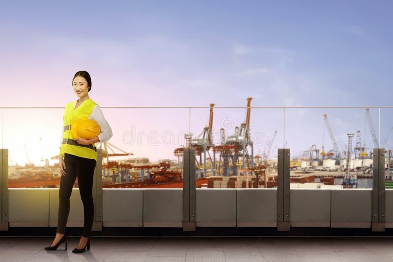 有举行在办公室大阳台的安全背心的俏丽的亚裔女工安全帽身分 免版税图库摄影