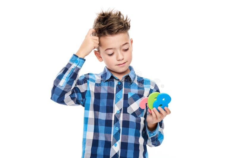 有举行大五颜六色的数字和抓他的头的dyscalculia的逗人喜爱的男孩 学习障碍概念 库存图片