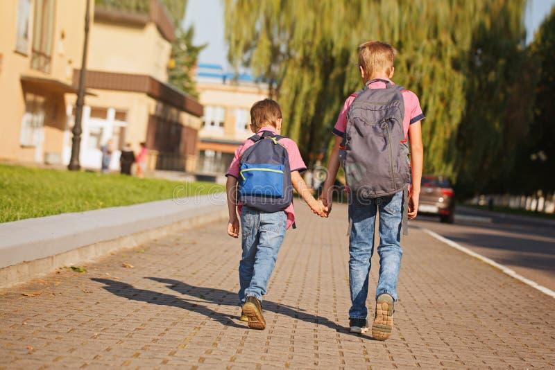 有举行的背包的两个小弟弟递走到学校 回到视图 免版税库存照片