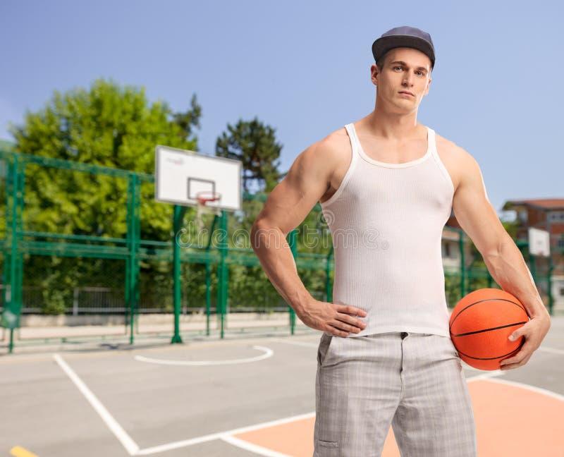 有举行篮球的蓝色焰晕的年轻人 免版税图库摄影