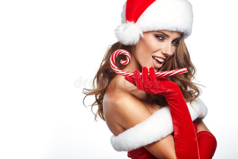 有举行红白的圣诞节的圣诞老人服装的美丽的妇女 库存图片