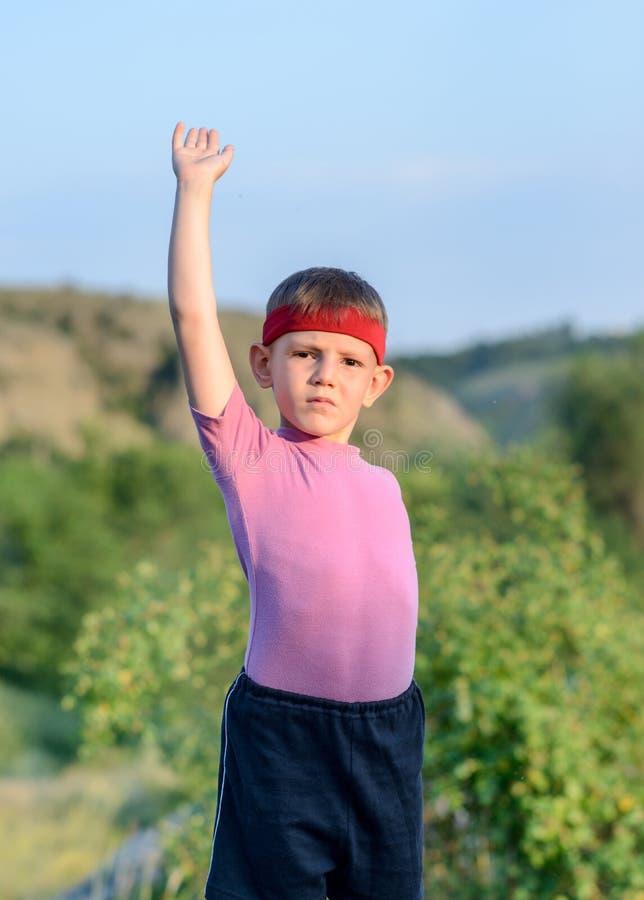 有举他的一条胳膊的头饰带的年轻男孩 免版税库存图片