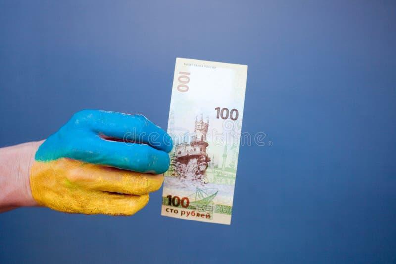 有乌克兰旗子的图画的男性手拿着100卢布 库存图片