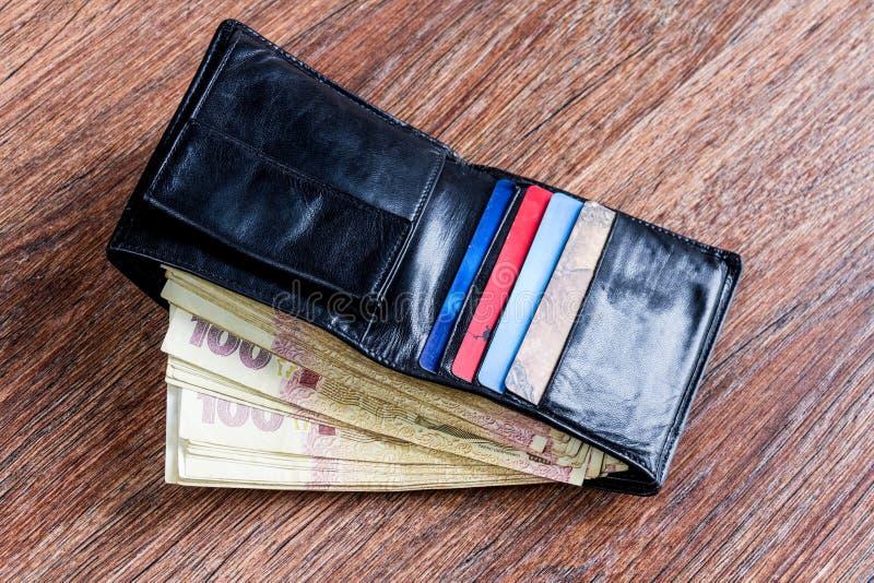 有乌克兰金钱和信用卡的皮革黑钱包 库存图片