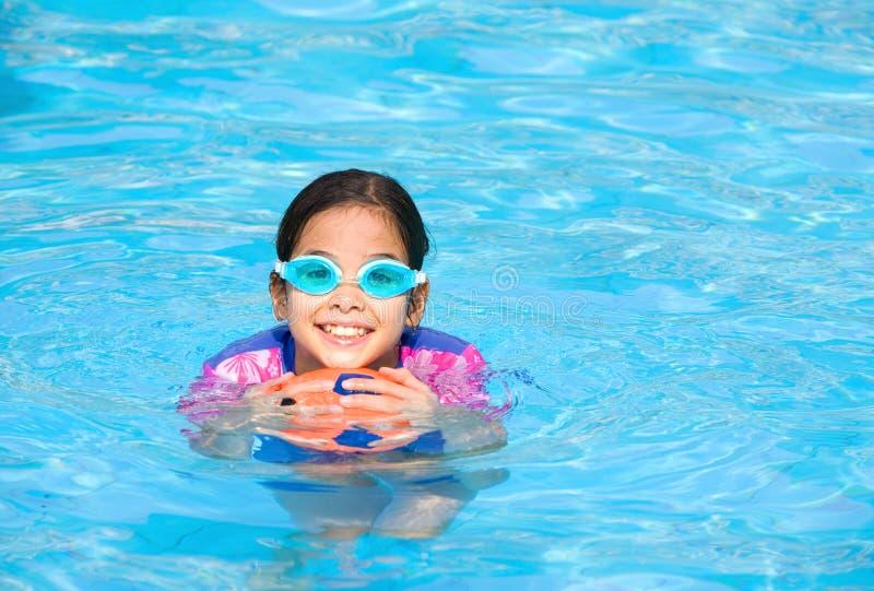 有乐趣的女孩演奏池游泳 库存图片
