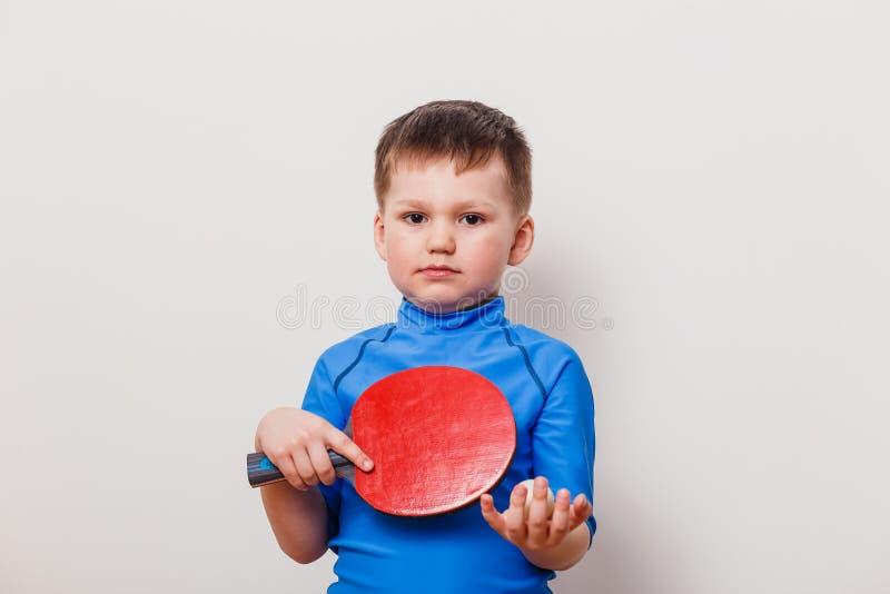 有乒乓球球拍的四岁的男孩 免版税库存照片