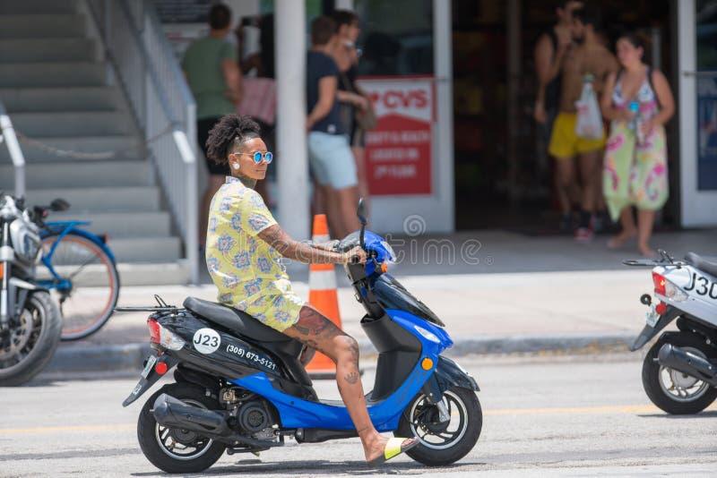 有乘坐在一辆滑行车的纹身花刺的妇女在海洋驱动的迈阿密海滩 免版税库存照片