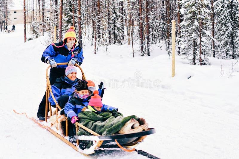有乘坐多壳的狗雪撬的孩子的家庭在芬兰在拉普兰在冬天 免版税图库摄影