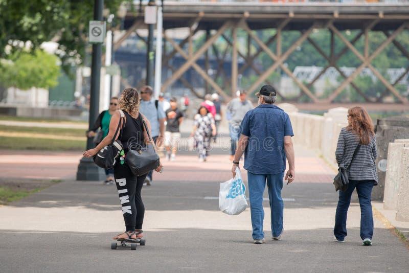有乘坐滑板的两个袋子的深色皮肤的妇女 库存图片