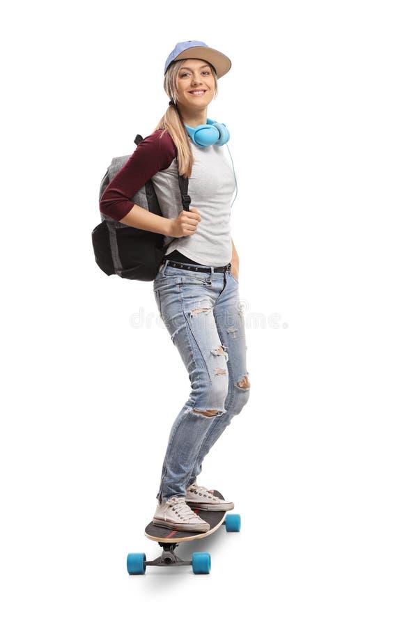 有乘坐longboard的背包的女性溜冰者 免版税库存照片