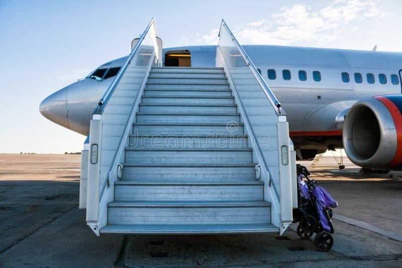 有乘客搭乘的飞机在与为孩子支架准备的婴儿推车的机场围裙跨步  免版税库存照片