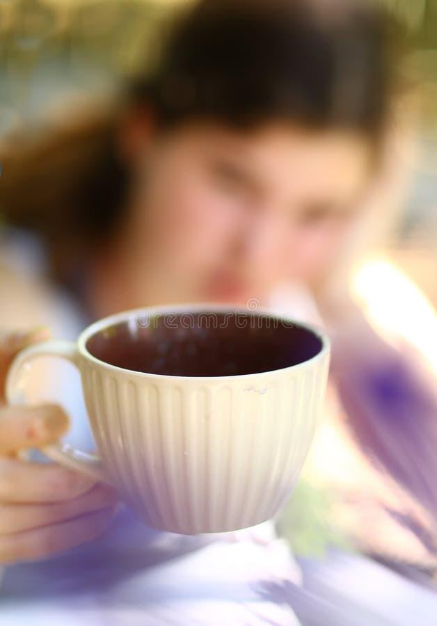 有书举行茶杯关闭的青少年的女孩照片 库存照片