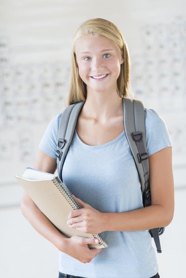 有书包的在化学班的学生和书 免版税图库摄影