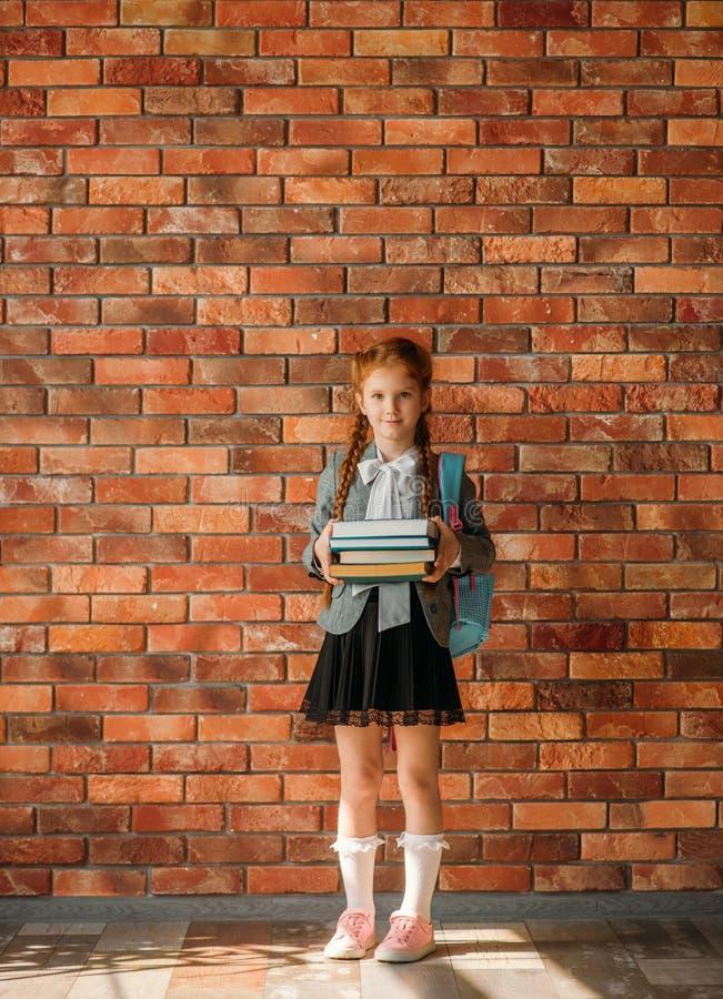 有书包的女小学生拿着堆课本 免版税图库摄影