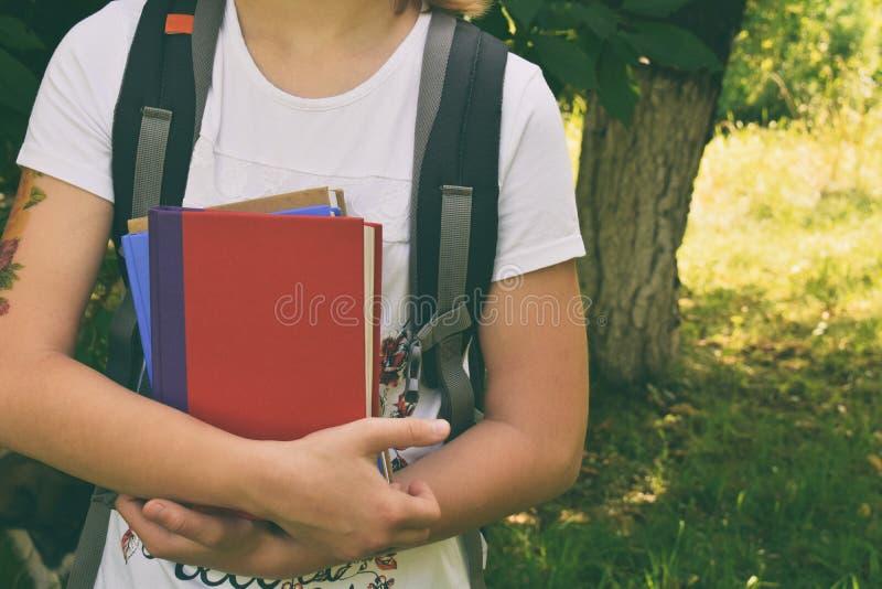 回到学校概念 有书包的少年在手上的拿着书 免版税库存照片