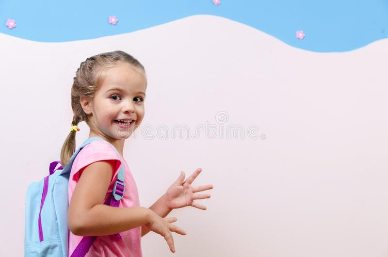 有书包的逗人喜爱的小女孩 免版税图库摄影