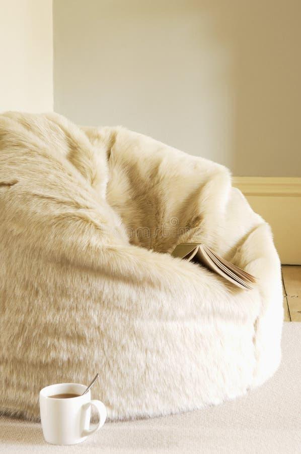 有书和咖啡杯的毛茸的装豆子小布袋 免版税图库摄影