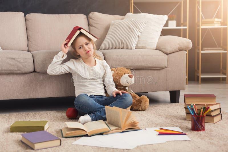 有书和玩具的哀伤的矮小的女孩 免版税库存照片
