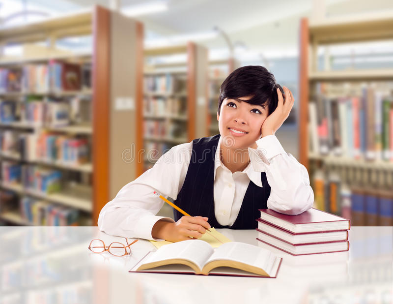 有书和纸的混合的族种青少年的学生作白日梦在图书馆里的 库存照片