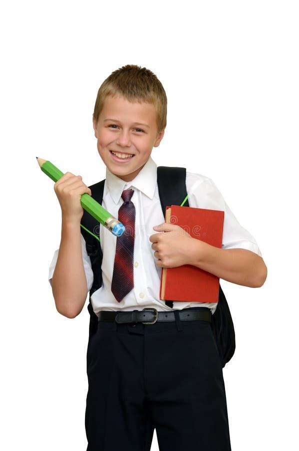 有书和铅笔的男小学生 免版税库存照片