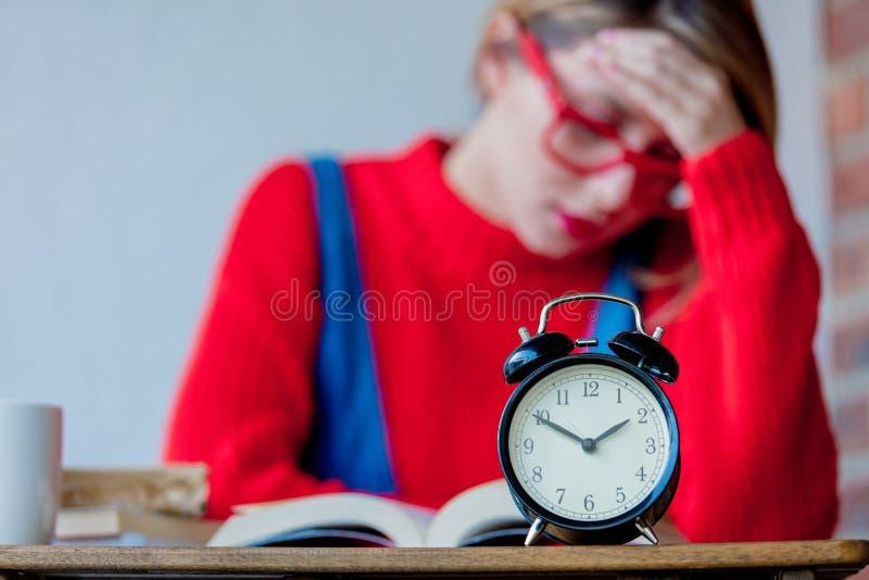 有书和闹钟的疲乏的女孩 免版税库存图片