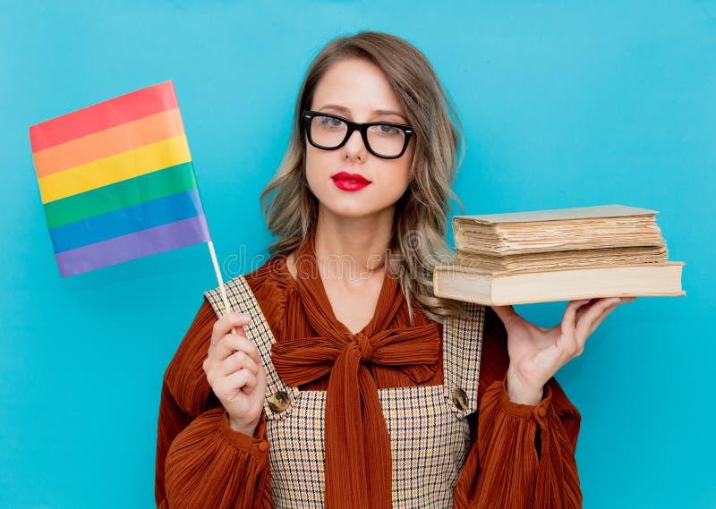 有书和LGBT旗子的年轻女人 库存图片