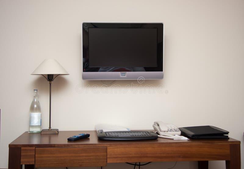 有书桌键盘电话灯和lcd电视机的书房 库存照片