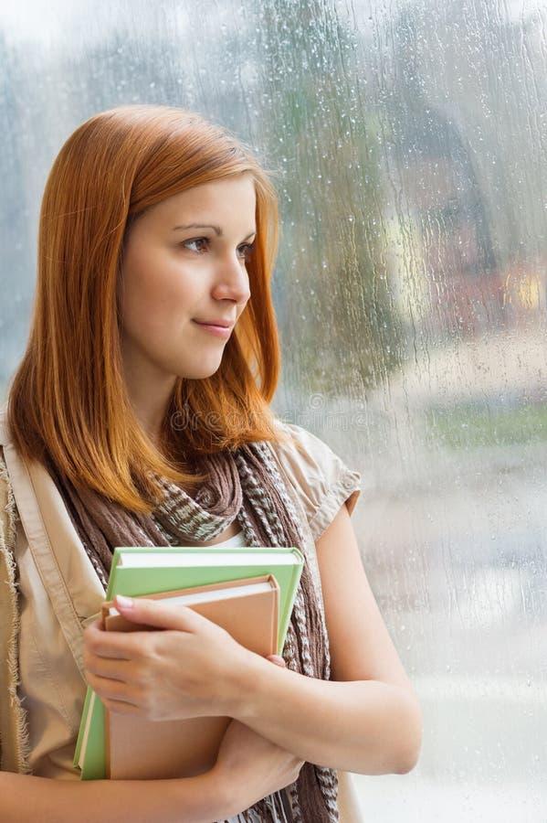 有书的体贴的学生由窗口 库存图片