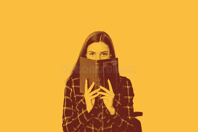 有书的俏丽的少年女生在她的掩藏与拷贝空间的手上面孔 库存照片