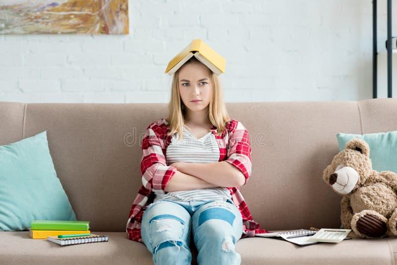 有书的哀伤的青少年的学生女孩在头在家坐长沙发和看 免版税库存图片