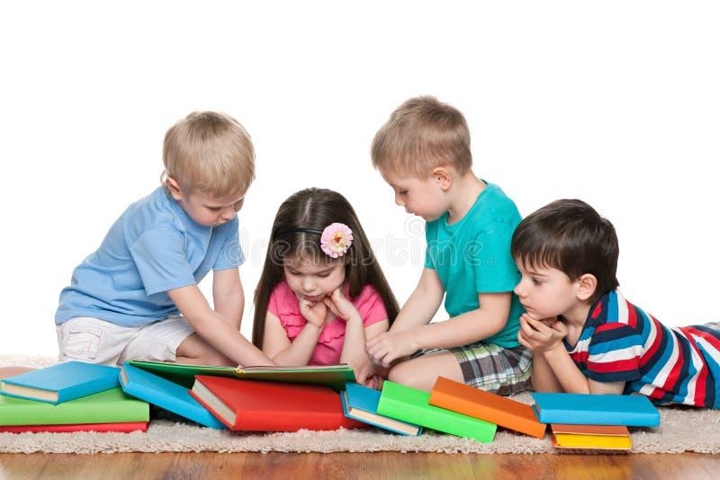 有书的四个孩子在地板上 免版税库存照片