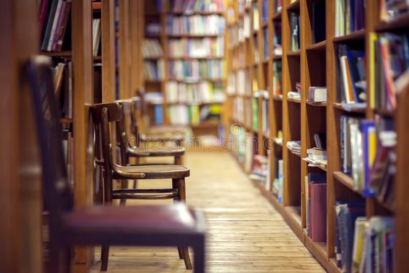 有书的图书馆在架子和空的椅子 免版税库存照片