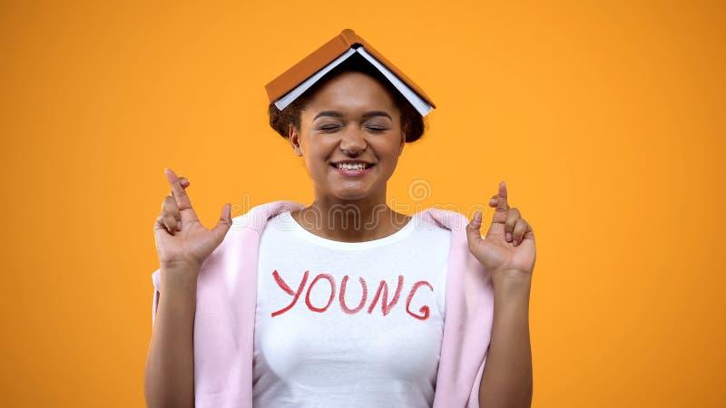 有书的在她的顶头横渡的手指,更好的记忆的学生仪式女孩 图库摄影