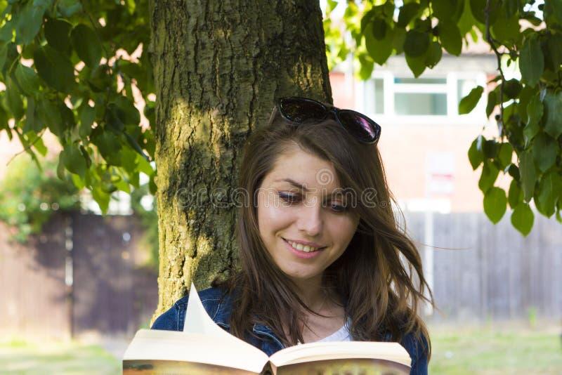 有书的女孩在夏天公园 免版税图库摄影