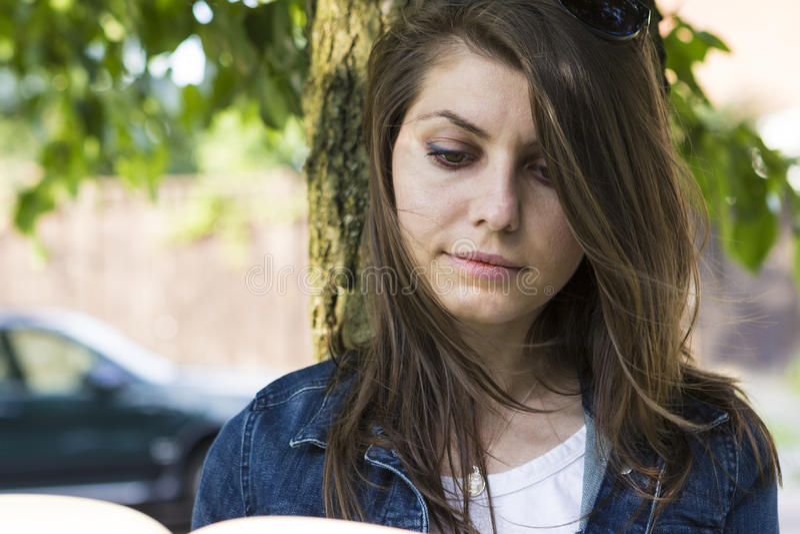 有书的女孩在夏天公园 免版税库存照片