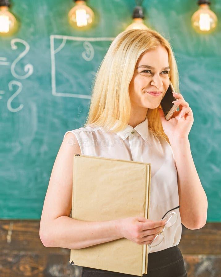 有书的妇女谈话在手机在教室 解决在电话,黑板的笑容的老师问题  免版税库存图片