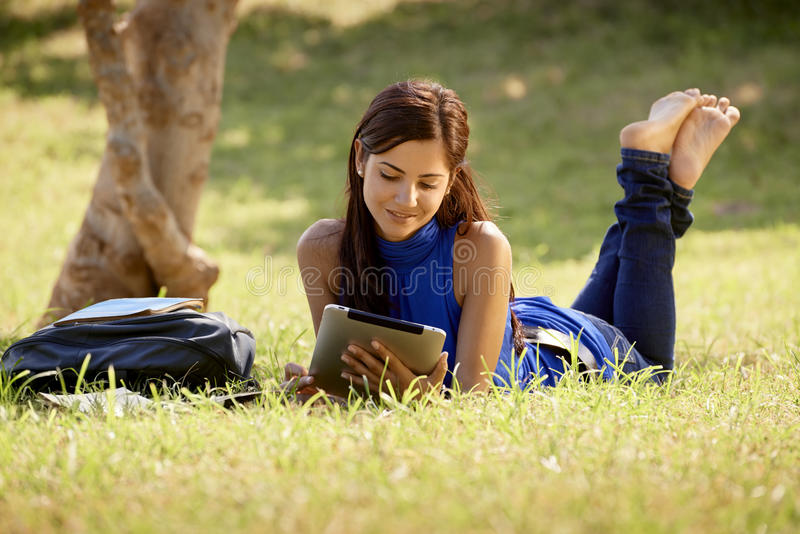 有书的学习为学院的妇女和ipad测试 免版税库存照片