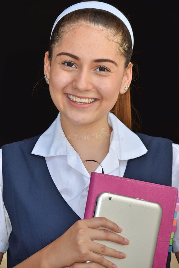 有书的宽容哥伦比亚的女学生微笑的佩带的制服 图库摄影