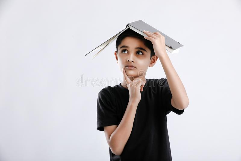 有书的小印度/亚裔男孩在头和严肃认为 库存照片