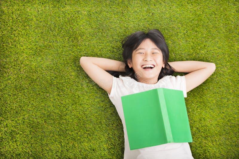 有书的小女孩和基于草 库存图片
