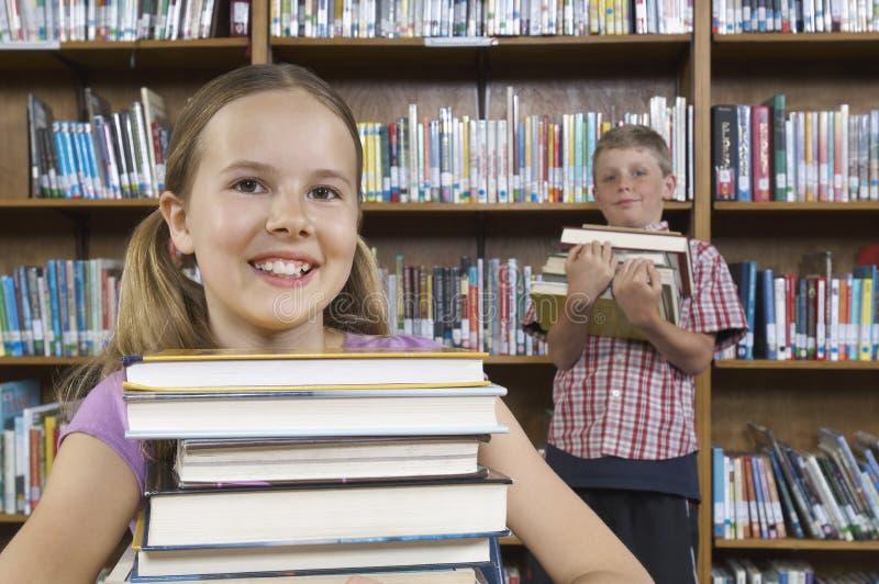 有书的小学生在图书馆里 图库摄影